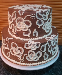 "11""x4"" and 8""x4"" Koko Samoa Cake with Koko Samoa Buttercream filling and Chocolate Buttercream exterior with Vanilla Buttercream brush embroidery flowers."